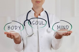 a woman naturopath holding the words body soul mind in her hands